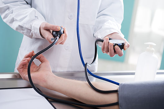 doctor taking blood pressure as part of illness treatment