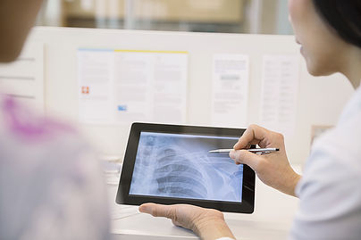 Doctor looking at digital X-rays at MEDIQ Urgent Care